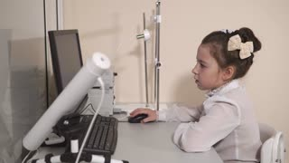 Young little girl is sitting alone at the computer in the office. She is using mouse and looking at the screen.