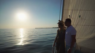 Young loving couple is spending summer evening on a pleasure boat. They are on a nose near a masts and sails, looking on a sea and chatting at ease