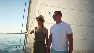 Young loving couple standing on the front deck of sailboat. Romantic date on the yacht