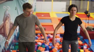 Young man and woman are standing close to each other on a platform. They are falling freely in soft pit.
