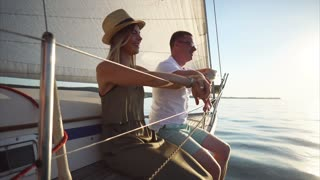 Young man and woman traveling along the river by yacht. They sitting on the board and enjoying nature scene