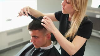 Young man getting haircut by female hairdresser while sitting in chair. Barber using scissors and comb