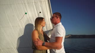 Young man is hugging him young beloved woman during their romantic date in luxury yacht. They are looking to each other and laughing, sun is reflecting from sea surface and illuminating their faces