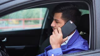 Young modern muslim businessman talking on smartphone in the car. Arab man nowadays.