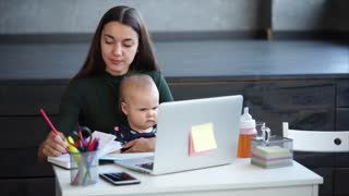 Young mother comes at work with her little daughter. She is reading from the monitor and writing information down. Her child is quietly sitting on mom's laps.