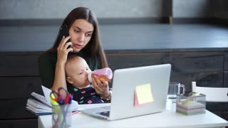 Young mother is giving juice to her baby from bottle and speaking by telephone. A woman on maternity leave is working from home, doing important phone call, holding baby, sitting in front of laptop.