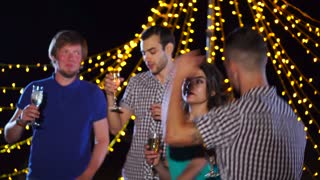 Young people relaxing, dancing and having alcohol drinks during night outdoor party