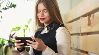 Young pretty and nice woman looks at photos and puts the likes of social networks on a mobile phone. A lady with red lipstick smiles, watching the news on the smartphone.