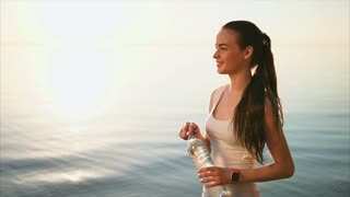 Young pretty sporty woman drinking clean water from the plastic bottle standing near the sea after jogging. Female wear smart watches. Water balance. Strong back light and lens flare. Steadicam shot.
