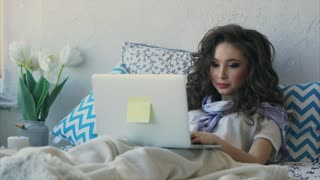 Young pretty woman freelancer working with her laptop at home in the bedroom. She is comfortable sitting on her bed.