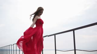 Young romantic girl is standing on a long wooden quay. She is looking to sea, touching her long red chiffon dress swaying by wind