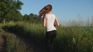 Young sport woman jogging on the nature. View from the back.