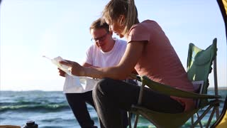 Young spouses who came to the sea in the summer, discuss the route of their journey, a man and a woman hold a paper map in their hands, a strong wind disturbs
