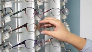 Young visitor woman of shop of spectacles is inspecting rim for glasses. She is considering frames fixed on showcase, close-up of hand
