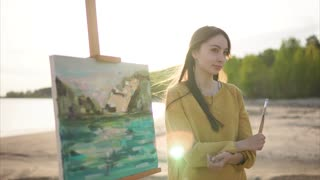 Young woman artist and her canvas painted en plein air against bright sunlight, water and green nature