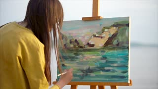 Young woman artist painting from nature passionately. Creating artwork outdoor on the river bank