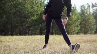 Young woman in sportswear training in the park. She doing side bend stretching exercise