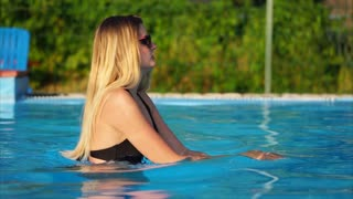 Young woman in sunglasses swimming in the pool with clear blue water. Refreshing in cool water on hot summer day