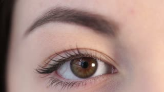 Young woman is closing her dark eye calmly, close-up