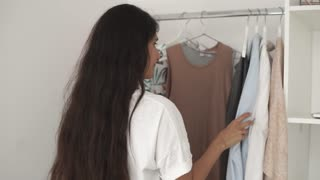 Young woman is deciding what to wear in morning. She is taking clothes from rack and trying on her body