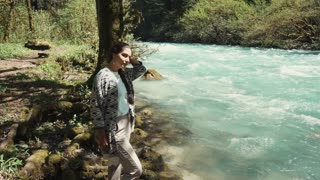 Young woman is relaxing and rejoicing sun and summer, standing in woodland. She is looking on amazing transparent water of mountain river