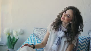 Young woman listening to music on headphones on a mobile phone and cheerfully singing along. Beauty with curly hair dances to the song, shaking her head from side to side.