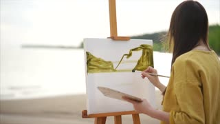 Young woman painter drawing watercolor landscape picture on easel. Beach of the lake