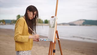 Young woman painter performing picture of landscape on the bank of the river. Countryside on background