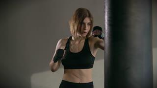 Young woman training punching bag boxing in fitness studio HD
