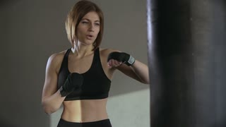 Young woman training punching bag boxing in fitness studio slow motion