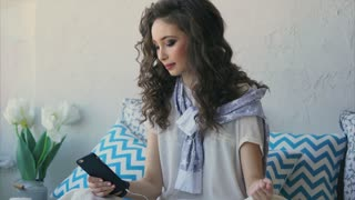 Young woman with curly hair listening to her favorite music in headphones on a mobile phone. She sits on the bed in her bedroom and enjoys the morning, slowly dancing.