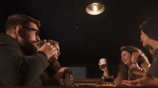 young women and men drink alcoholic and non-alcoholic drinks in a trendy bar, old friends laugh at a meeting and socializing in a public place
