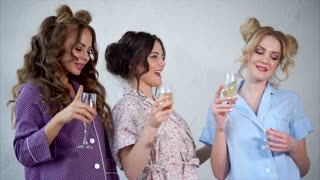 Young women who are dressed in pajamas are dancing with glasses of champagne in their hands. Happy friends with make-up and stylish hairstyles having a fun on a pajama party in the bedroom.