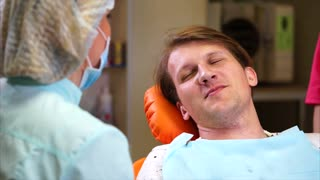 Zoom out of a happy man patient listening to dentist consultation after teeth treatment