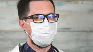 Zoom out of man doctor wearing glasses and medical face mask. He staring to the camera with warning and strict look