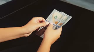 Woman hands count earnings a pack of dollars on the black background
