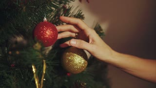 Woman hands play with ball on christmas tree close up