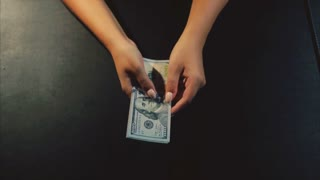 Woman hands showing a fan of dollar bills on the black background