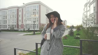 Woman in black hat and glasses talking on cellphone outdoor