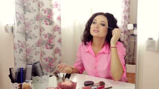 Woman makeup make-up applying mascara looking at the mirror
