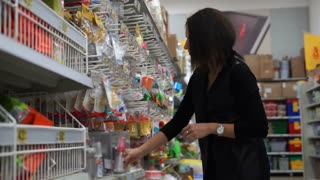 Woman mother in a supermarket chooses a small bottle for feeding of the child
