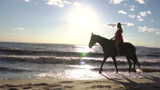 Woman riding on horse at river beach in water sunset light