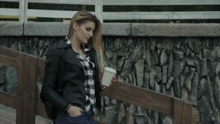 Woman with a cup of coffee outdoor. Pretty girl enjoying her morning.