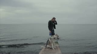 Young attractive woman with siberian husky dog stand on the coast of the sea