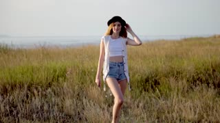 Young beautiful girl model in hat runnig and dancing on meadow near the river