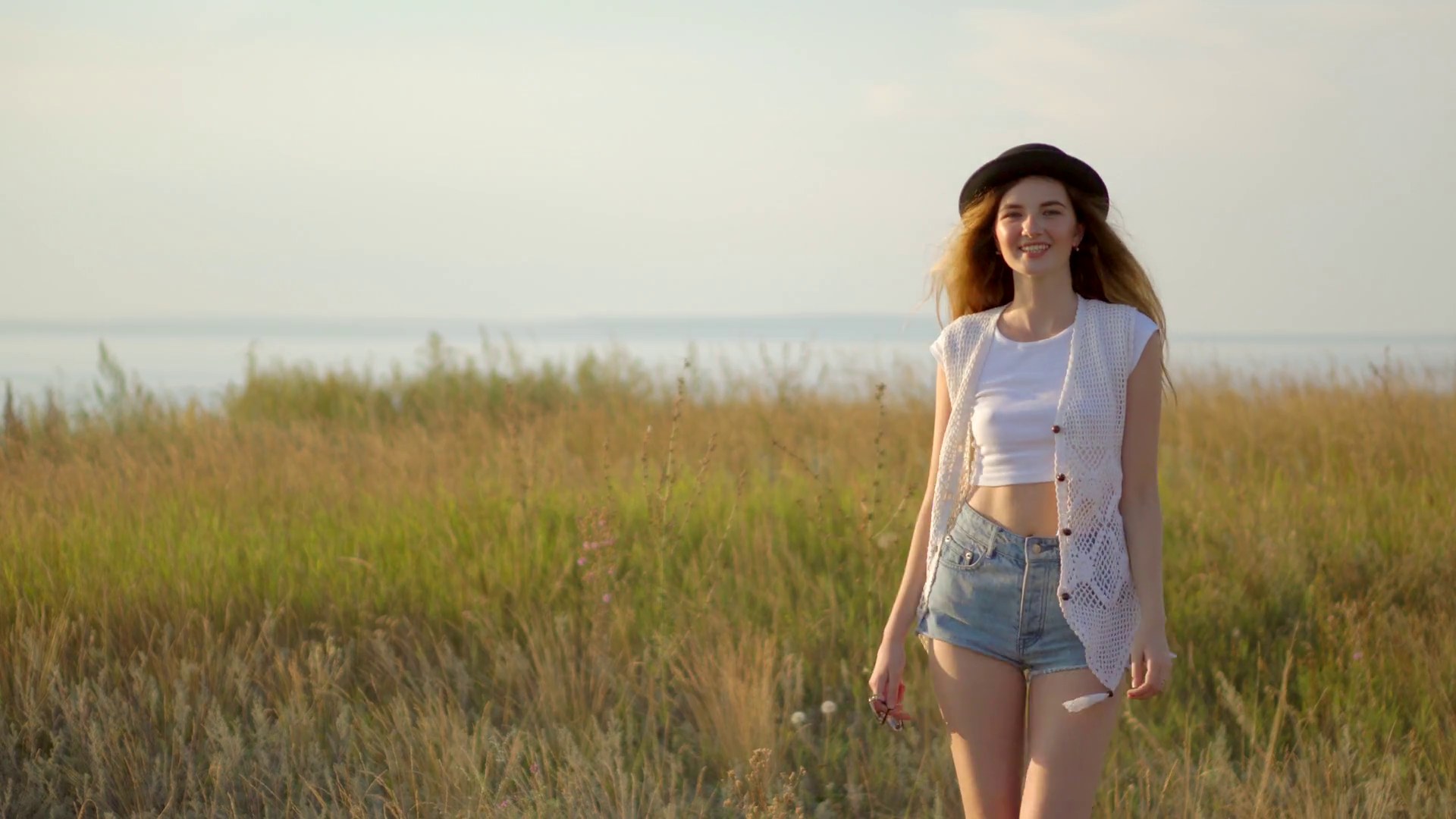 Young beautiful girl model in hat walking and posing on meadow near the river Stock Video Footage - Storyblocks