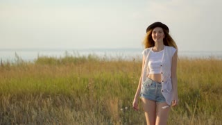 Young beautiful girl model in hat walking and posing on meadow near the river