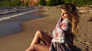 Young beautiful girl sitting on the river side sheltered plaid enjoying sunset