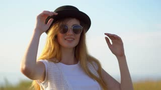 Young beautiful woman model in hat and sunglasses posing and smiling outdoor