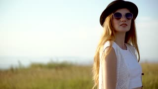 Young beautiful woman model in hat and sunglasses posing outdoor slow motion